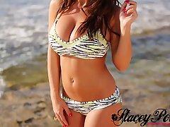 Молодая девушка на фотосессии в бикини на пляже показывает большие дойки