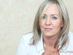 Зрелая блондинка частично раздевается перед камерой и ласкает свой клитор