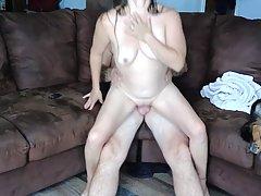 Зрелая женщина и ее любовник на диване занимаются съемками д...