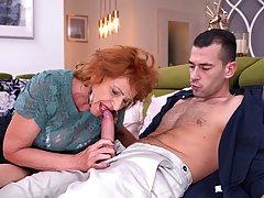 Зрелая женщина с рыжими волосами ублажает на диване длинный ...